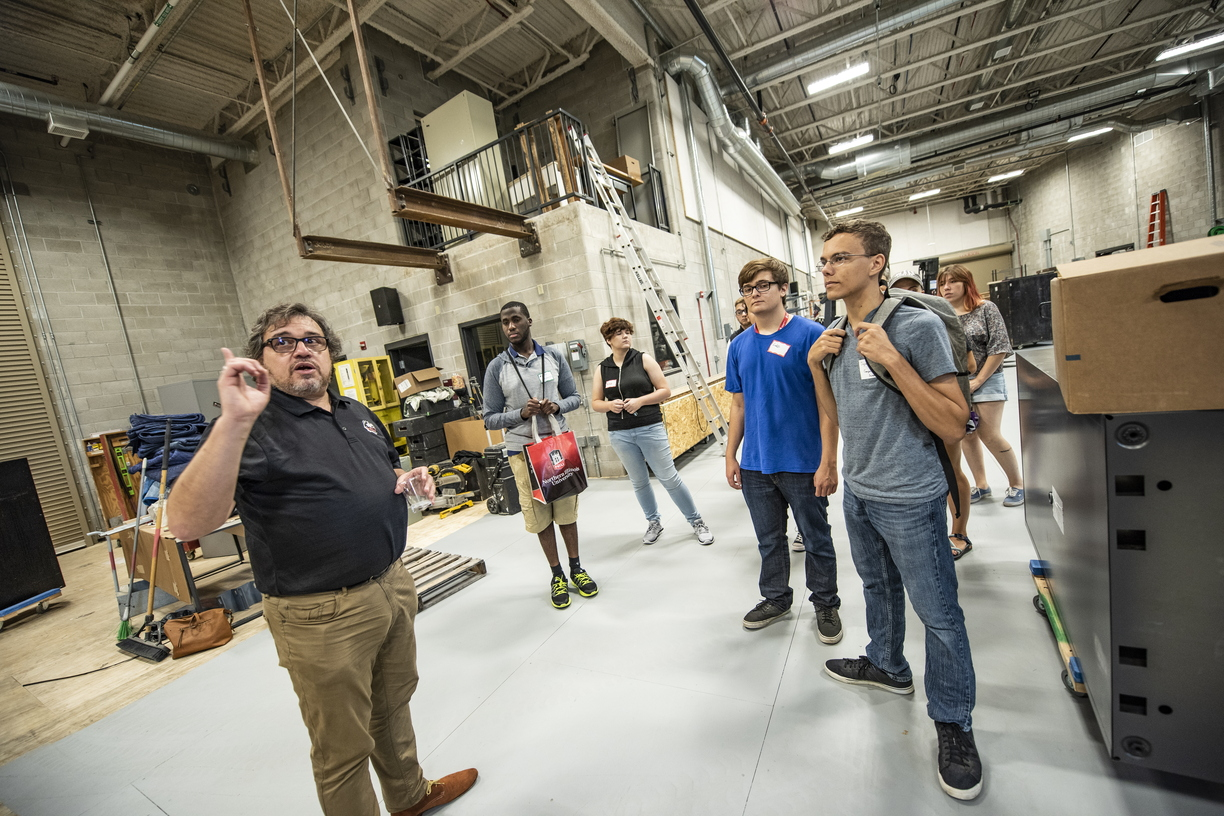 Gelman tour students in scene shop in Stevens